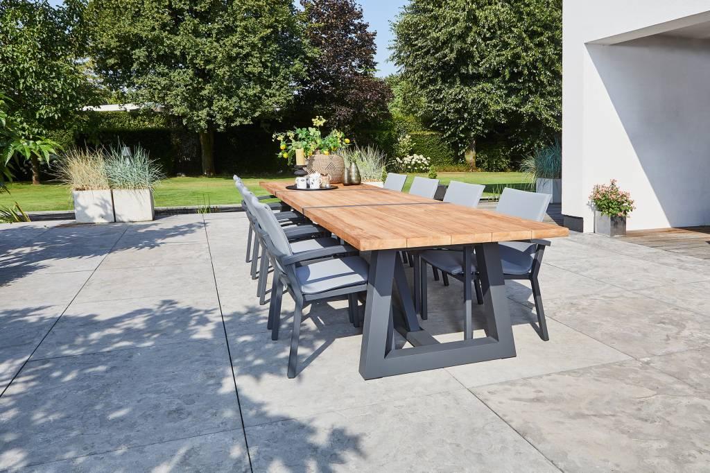 Grote tuintafel met zwarte poten en een houten blad geplaatst op een terras met grote vierkante antraciet tegels