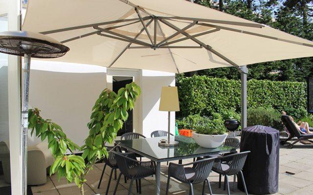 Beige zweefparasol op een witte stenen terras in zonnig weer