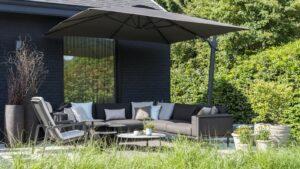 Een antraciet loungeset in een groene omgeving onder een bruine zweefparasol