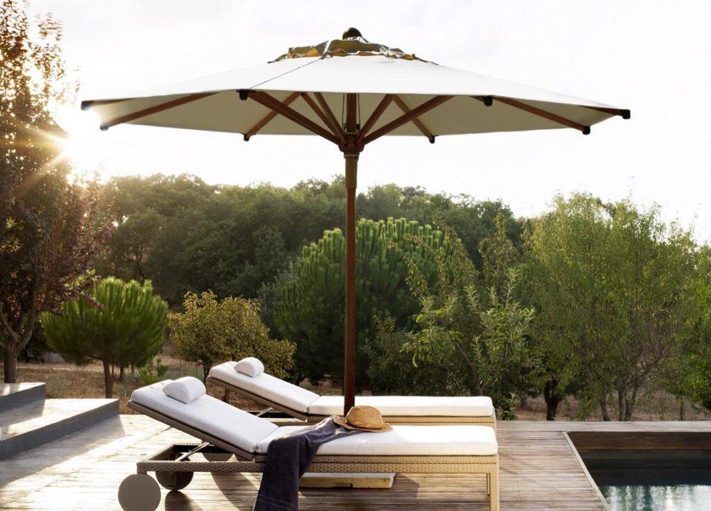 Een beige sta parasol op een houten flonde naast 2 bedden aan het zwembad
