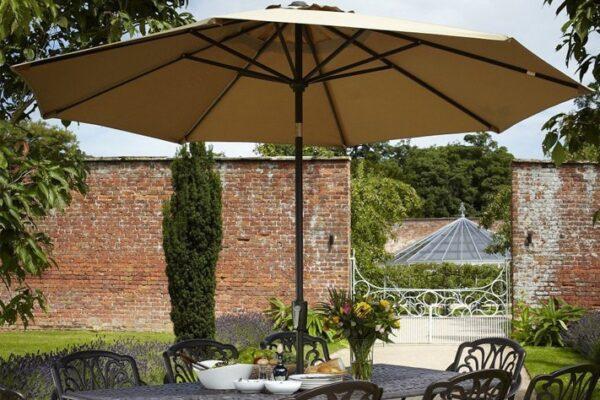 Klassieke wit creme achtige parasol op een terras omring met een bakstenen muur