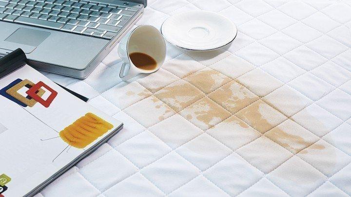 Koffie mok die om is gevallen en een vlek achter heeft gelaten op een wit kussenlaken