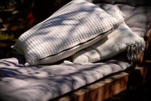 Close up van een loungekussens die op een houten loungeset ligt