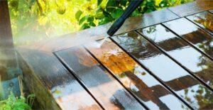 Hoge drukspuit die de groene aanslag verwijderd van een houten tafel